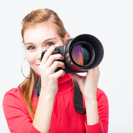 Pretty, female photographer with her digital camera (color toned image; shallow DOF) photo