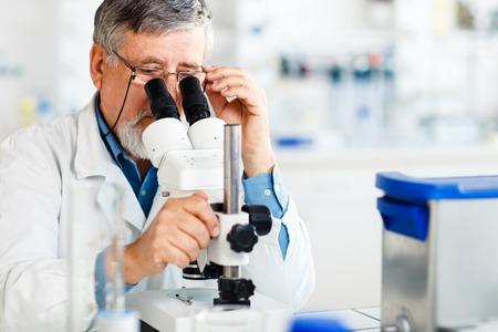 senior mannelijke onderzoeker verrichten van wetenschappelijk onderzoek in een laboratorium met behulp van een microscoop (ondiepe DOF, kleur getinte afbeelding)