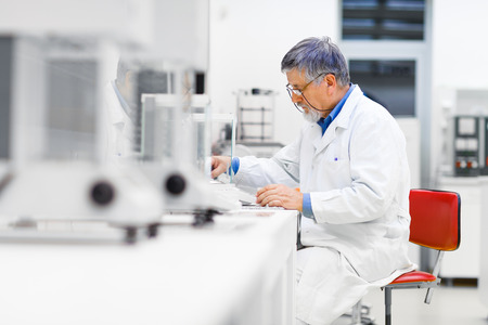 scientific equipment: Senior male researcher carrying out scientific research in a lab (shallow DOF; color toned image)