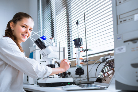 lab coat: Retrato de un estudiante de qu�mica llevar a cabo investigaciones en un laboratorio de qu�mica (imagen a color entonado, DOF bajo) Foto de archivo