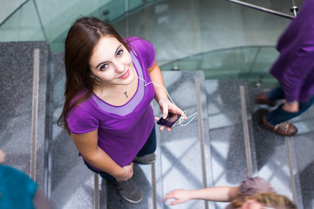 adulthood: At the universitycollege - Students rushing up and down a busy stairway - confident pretty young female student looking upwards while listening to music on her mp3 player (color toned image)