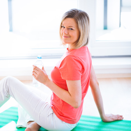 Pretty young woman refreshing during workout at home photo