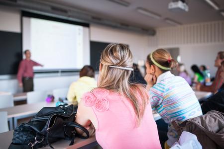 Studenten zitten in een klaslokaal tijdens de les (ondiepe DOF, kleur getinte afbeelding) Stockfoto