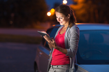 distraction: Pretty, female driver using her tablet computer (shallow DOF; color toned image)