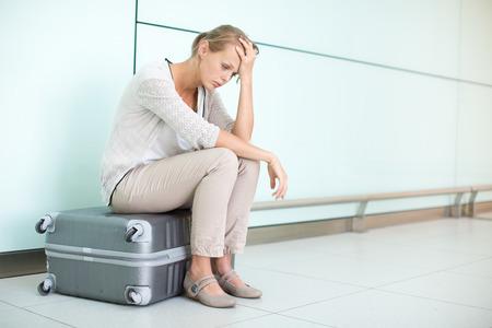 Jung, weiblich frustriert Fluggast am Flughafen und wartete verzweifelt nach ihrem verspäteten Flug (Farbe getöntes Bild, flache DOF)