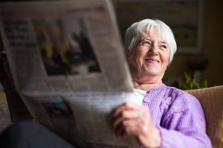 Senior femme lisant le journal du matin, assis dans son fauteuil préféré dans son salon, l'air heureux Banque d'images