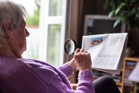 Senior woman reading morning newspaper, sitting in her favorite chair in her living room, looking happy Stock Photo - 39041597