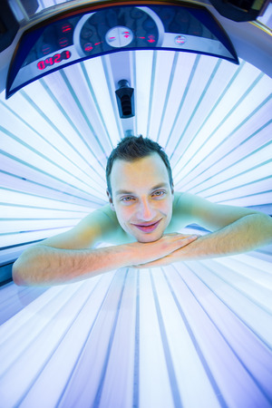 sunspot: Handsome young man relaxing during a tanning session in a modern solarium, taking care of himself, enjoying the artificial sunlight.
