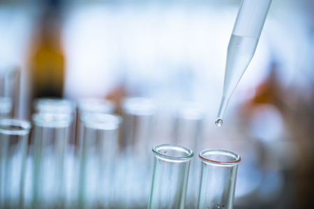 Gota de líquido de la pipeta de vidrio de laboratorio al tubo de ensayo. Foto de archivo