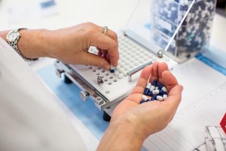 의료 약 산업 공장과 실내 생산, 약을 처리하는 작업자의 손