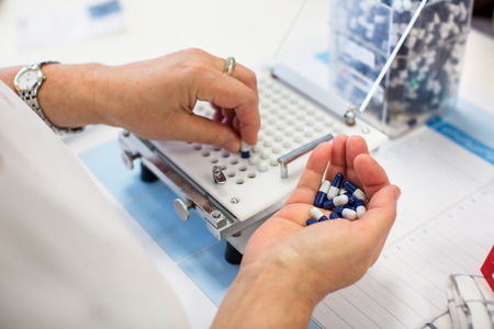 manufacture: medical pills industry factory and production indoor, workers hands handling pills Stock Photo