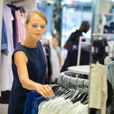 Beautiful young female shopper in a clothing store, chossing a blouset-shirtgarments (shallow DOF; color toned image) photo