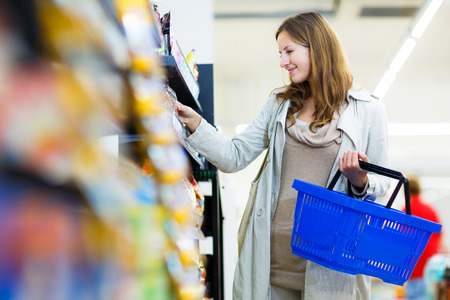groceries: Beautiful young woman shopping in a grocery storesupermarket (color toned image)