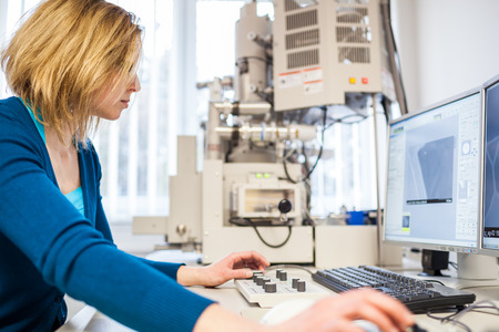 Pretty, female researcher using a microscope in a lab, doing research (color toned image) photo