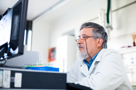 phisician: Senior researcher using a computer in the lab while working on an experiment (color toned image)