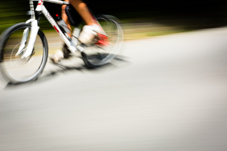 convey: Cyclist on a road bike going fast (motion blur technique is used to convey movement; colour toned image)