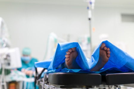 catling: Feet of a patient ready  for a surgery in a surgery room (color toned image; shallow DOF)