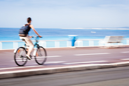 fast lane: Great way to get around in a city -Motion blurred cyclist going fast on a city bike lane, by the sea shore Stock Photo