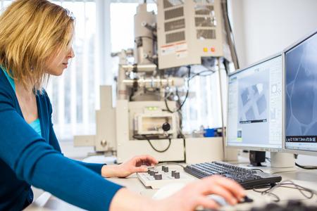 Pretty, female researcher using a microscope in a lab, doing research photo