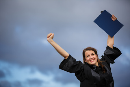 Pretty, young woman celebrating joyfully her graduation - spreading wide her arms, holding her diploma, savouring her success (color toned image; shallow DOF) photo