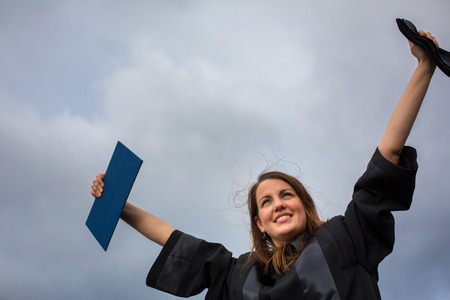 joyfully: Pretty, young woman celebrating joyfully her graduation - spreading wide her arms, holding her diploma, savouring her success