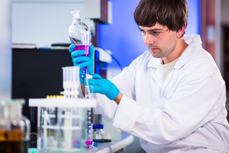 health care research: Young male researcher carrying out scientific research in a lab (shallow DOF; color toned image) Stock Photo