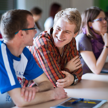 Handsome college student sitting in a classroom full of students during class  (color toned image; shallow DOF) Stock Photo
