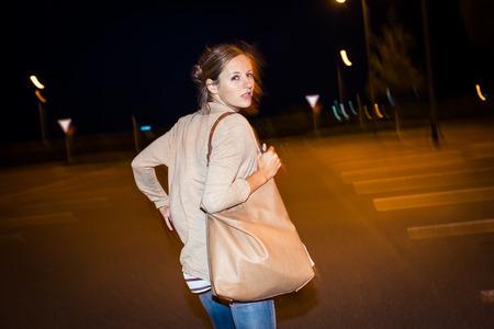人けのない駐車場で彼女の追手から実行している若い女性を怖がってください。