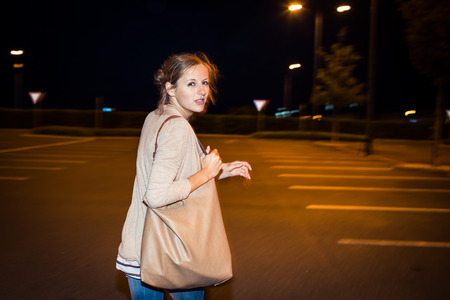 clinical psychology: Scared young woman running from her pursuer in a deserted parking lot
