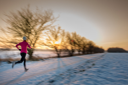 coutryside: Young woman stretching while running outdoors on a cold winter evening Stock Photo