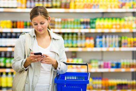 スーパー マーケットモール食料品店で食料品を買ってかなり若い女性 (色のトーンのイメージ; 浅い自由度)