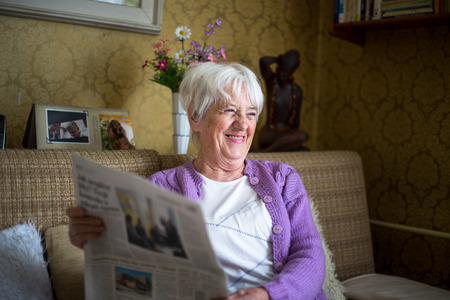 easy chair: Senior woman reading morning newspaper, sitting in her favorite chair in her living room, looking happy