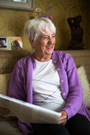 damas antiguas: Superior de la mujer leyendo el periódico por la mañana, sentado en su silla favorita en su sala de estar, con una mirada feliz