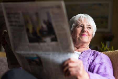 boomer: Senior woman reading morning newspaper, sitting in her favorite chair in her living room, looking happy