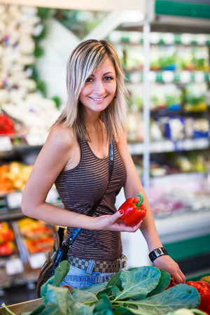 produce departments: Beautiful young woman shopping for fruits and vegetables in produce department of a grocery storesupermarket Stock Photo