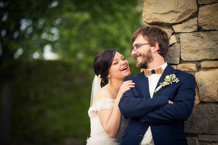 wedlock: Portrait of a young wedding couple on their wedding day, looking happy, laughing together instead of posing properly for the photographer Stock Photo