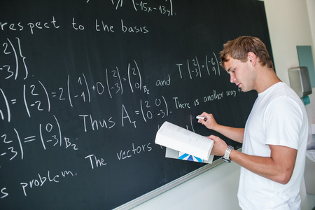 Handsome college student solving a math problem during math class in front of the blackboard/chalkboard (color toned image) photo