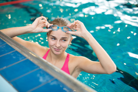 swimming race: Female swimmer in an indoor swimming pool - doing crawl (shallow DOF) Stock Photo