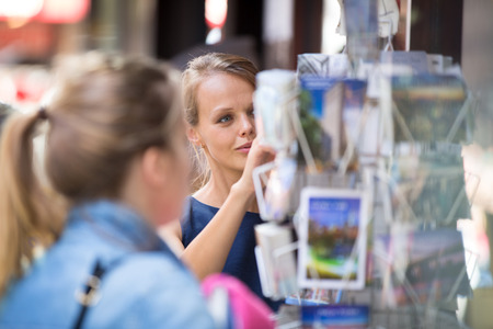 adress: Pretty, young woman buying a postcard on a street (shallow DOF) Stock Photo