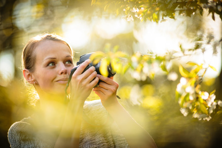 trees photography: Pretty female amateur photographer taking photos outdoors, doing what she loves to do
