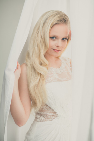 blonde woman: Gorgeous young womanbride wearing a lovely dress, in a window, hiding in curtains(color toned image; shallow DOF)