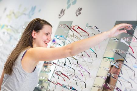 Jolie, jeune femme de choisir de nouvelles montures de lunettes dans un magasin opticien (image couleur tonique; shallow DOF)