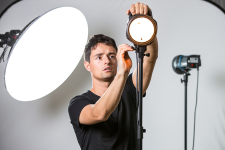 studio photography shot: Young, pro photographer setting lights in his well equiped studio before a photo shoot (color toned image; shallow DOF)