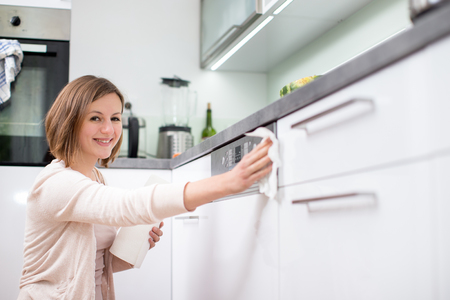 젊은 여자는 부엌 청소, 집안일을 하