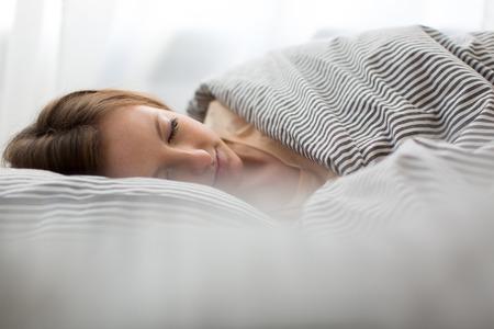 sono: Bela adormecida jovem mulher na cama
