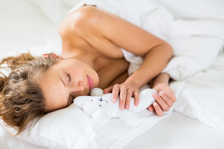 wellness sleepy: Beautiful young woman sleeping in bed, with her favorite pet toy, even though she is adult Stock Photo