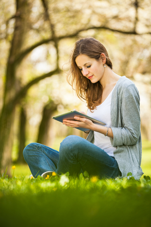 relaxation: Young woman using her tablet computer while relaxing outdoors in a park on a lovely spring day