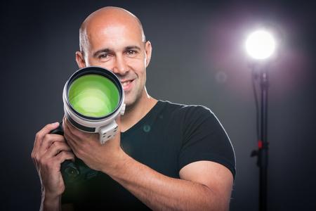 Jonge, professionele mannelijke fotograaf in zijn atelier tijdens een fotoshoot (kleur getinte afbeelding, ondiepe DOF)