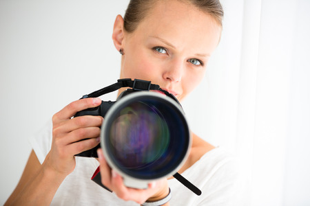 telephoto: Pretty, female photographer with digital camera - DSLR and a huge telephoto lens (color toned image; shallow DOF) Stock Photo