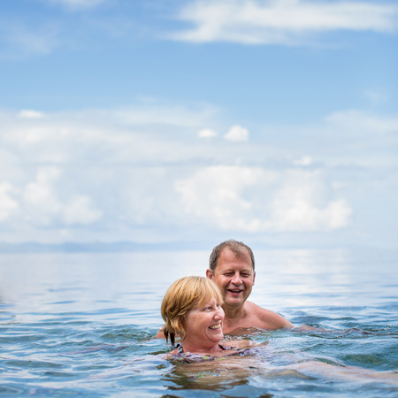 togther: Senior couple enjoying the retirement on a seacost, having a swim in the sea, laughing togther, staying active and positive